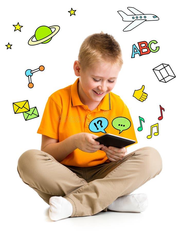 Caçoe o menino que senta-se com tablet pc e aprendizagem ou jogo imagem de stock royalty free