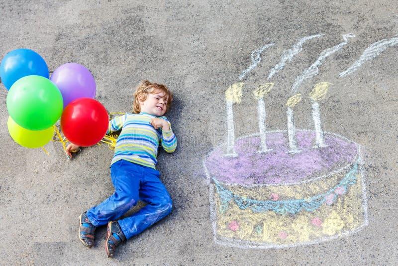 Caçoe o menino que tem o divertimento com o desenho colorido do bolo de aniversário com chal fotos de stock royalty free