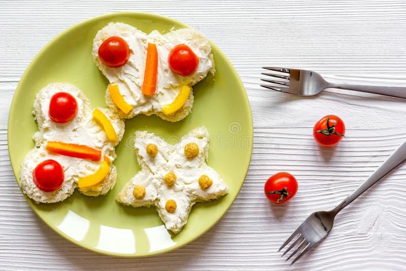 Caçoe a opinião superior dos sanduíches da borboleta do café da manhã no fundo de madeira fotografia de stock