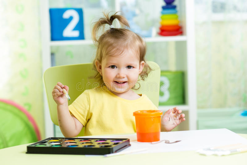 Caçoe a pintura da menina na tabela na sala de crianças fotografia de stock royalty free