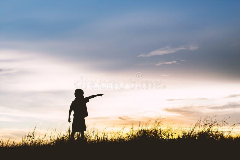 Caçoe a silhueta, momentos da alegria do ` s da criança procurando o futuro, fotografia de stock