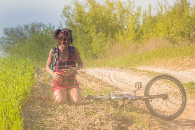 Caída bonita de la muchacha apenas de la bici de la bicicleta cerca del campo de trigo en los rayos solares La bicicleta miente e fotografía de archivo