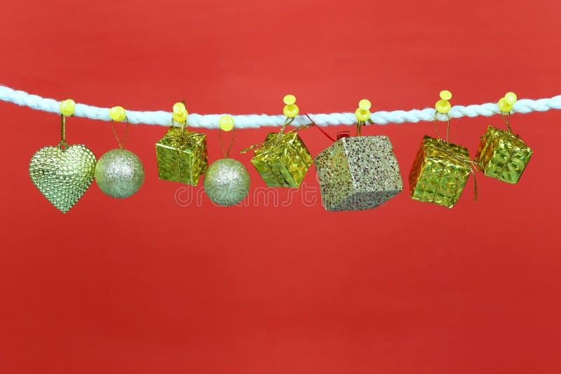 Caída de la caja de regalo del oro en la cuerda para tender la ropa y tener espacio de la copia con el fondo rojo imágenes de archivo libres de regalías