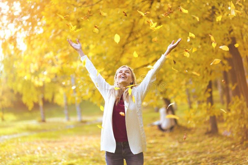 Caída de la hoja, mujer feliz en el parque del otoño imagen de archivo