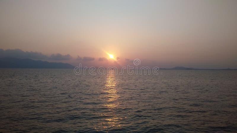 Caída de la puesta del sol en el mar en leanmgob imagenes de archivo