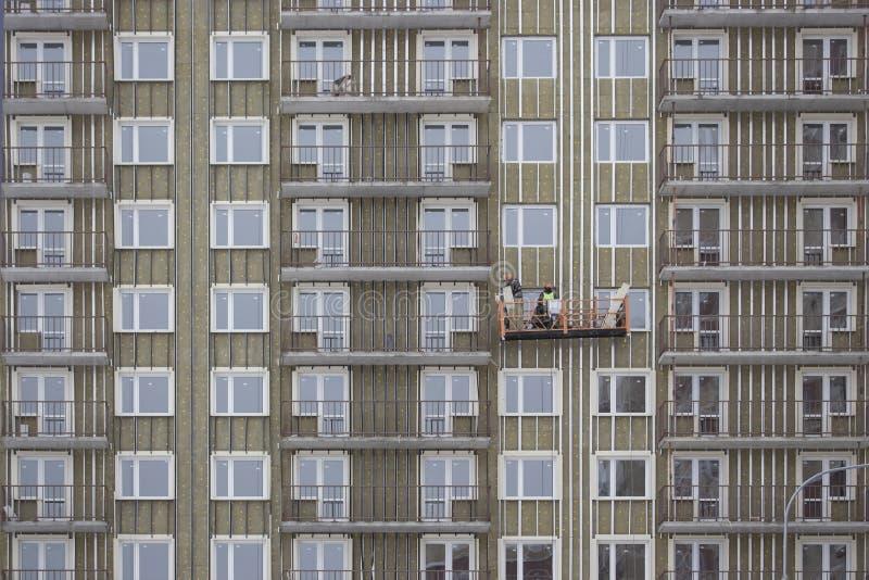 Caída del constructor en la cesta de una casa inacabada Construcción de un edificio alto de apartamentos residencial imagenes de archivo