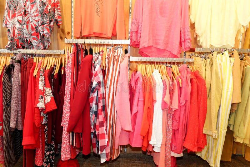 Caída del paño de las camisas del color en un estante en una tienda de la ropa de diseñador foto de archivo
