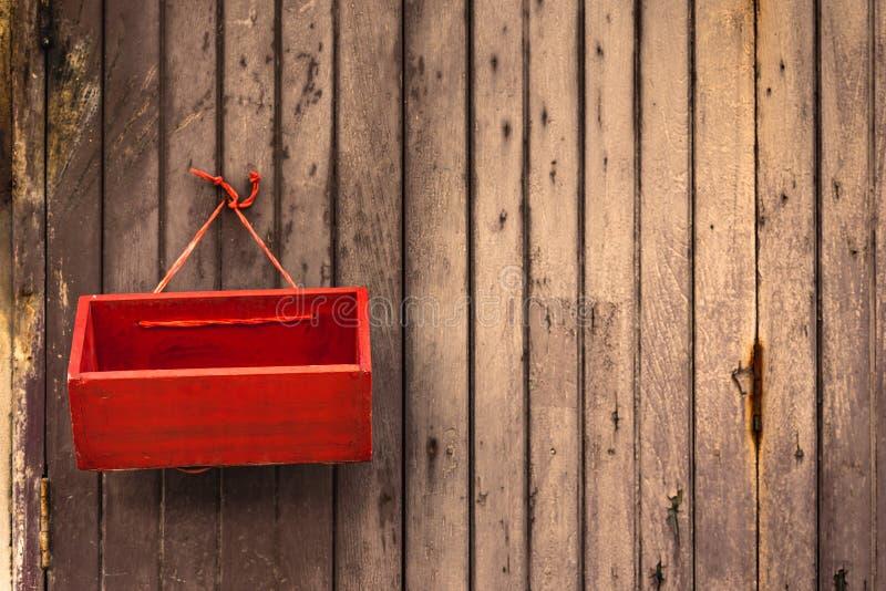 Caída roja de la caja en puerta de madera vieja fotos de archivo