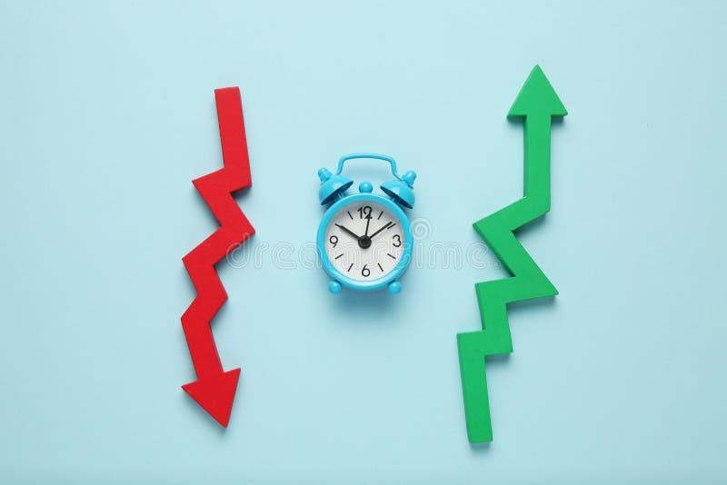 Caída y crecimiento en negocio Reloj, flecha roja abajo, verde - para arriba imagen de archivo