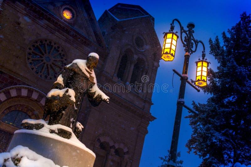 Caídas de la nieve pesadamente en esta escena de la noche de la basílica de St Francis y de St Francis de la estatua de Assisi en imágenes de archivo libres de regalías