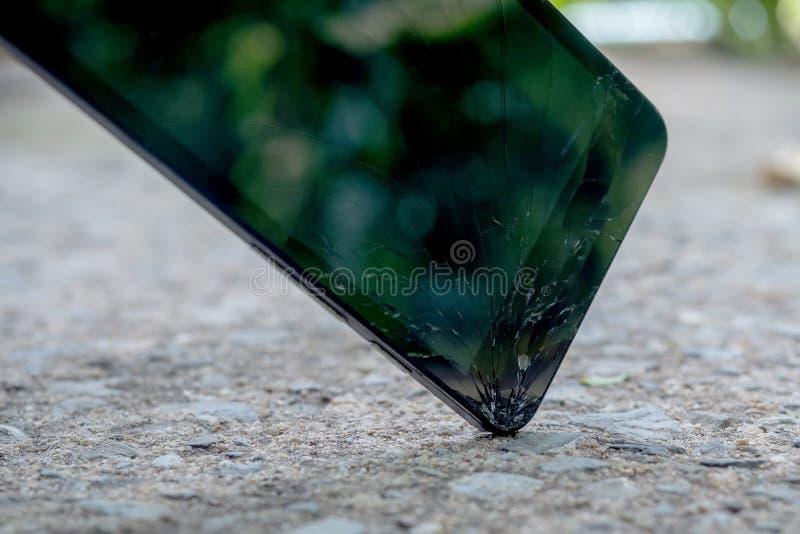 Caídas del teléfono celular que se estrellan al piso concreto foto de archivo
