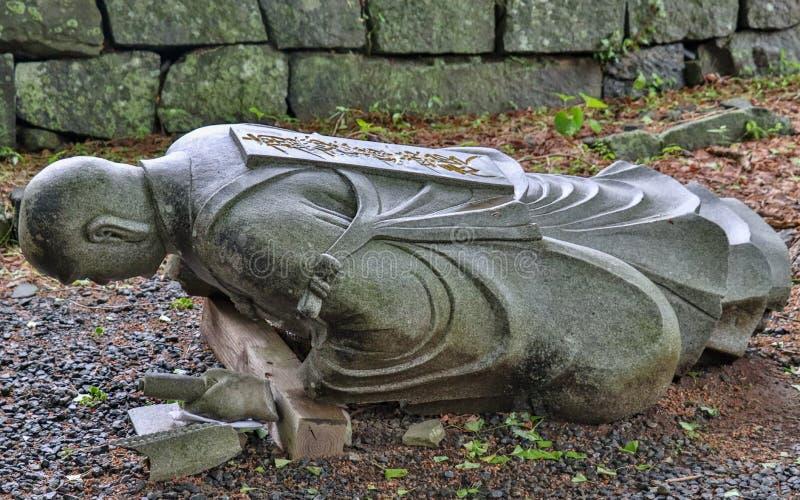 Caído abajo, piedra caida del granito del monje budista escultural en un templo en Japón Templo de Higo Honmyo, prefectura de Kum fotos de archivo