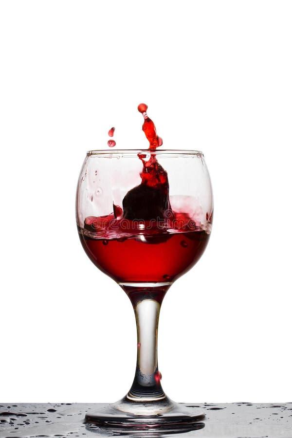 Caído en un vidrio de uvas formó un chapoteo del vino rojo brillante imagen de archivo
