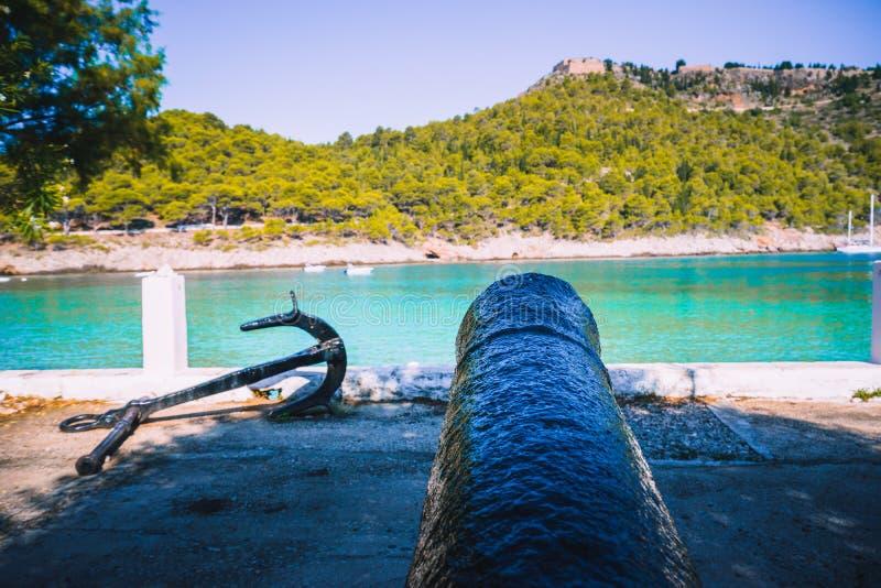 Cañón y ancla en la costa de la isla de Kefalonia en el pueblo de Assos Bahía del mar y arboleda tranquilas del pino del borrachí fotografía de archivo libre de regalías