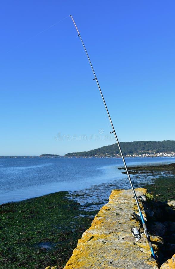 Caña de pescar azul en un embarcadero Pequeño pueblo costero, rocas, mar azul, día soleado Galicia, España fotos de archivo libres de regalías