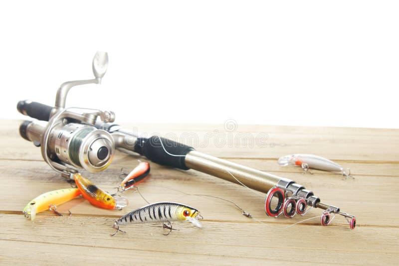 Caña de pescar con los diversos wobblers en una tabla de madera imagen de archivo