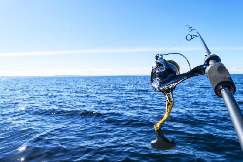 Caña de pescar que hace girar con la línea primer Caña de pescar en tenedor de barra en el barco de pesca debido el día de la ind fotografía de archivo libre de regalías