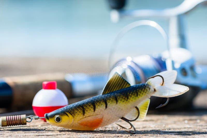 Caña de pescar, señuelo, y gancho en el embarcadero imagenes de archivo