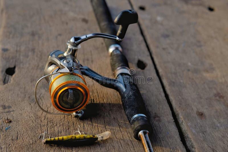 Caña de pescar y cebo de pesca en la tabla de madera fotos de archivo