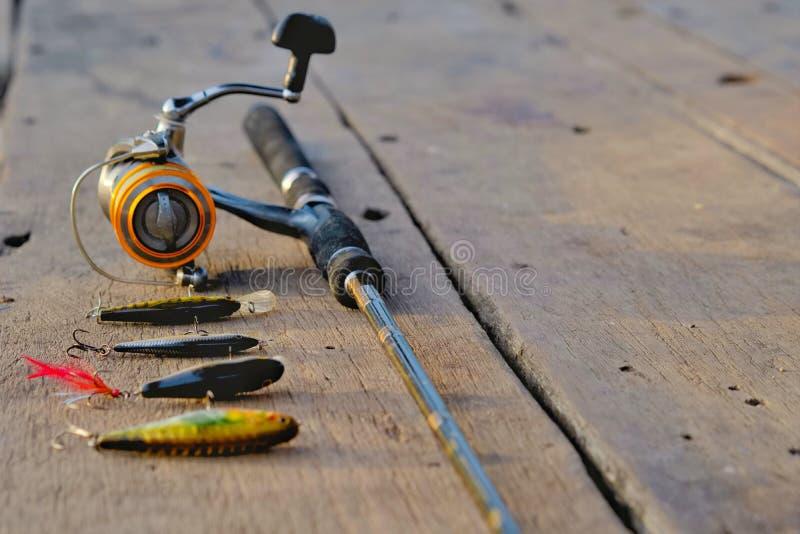 Caña de pescar y cebo de pesca en la tabla de madera fotografía de archivo