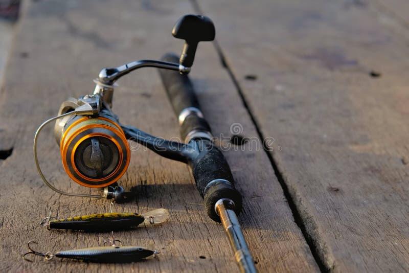 Caña de pescar y cebo de pesca en la tabla de madera foto de archivo