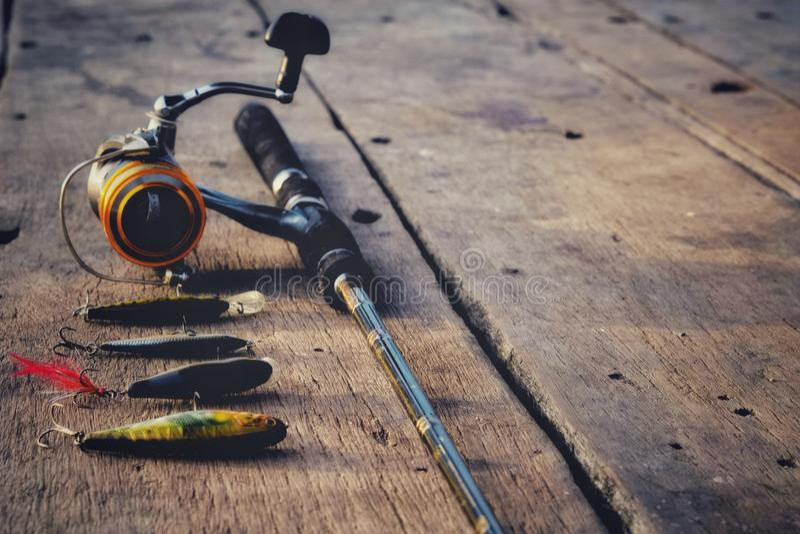 Caña de pescar y cebo de pesca en la tabla de madera imagen de archivo libre de regalías