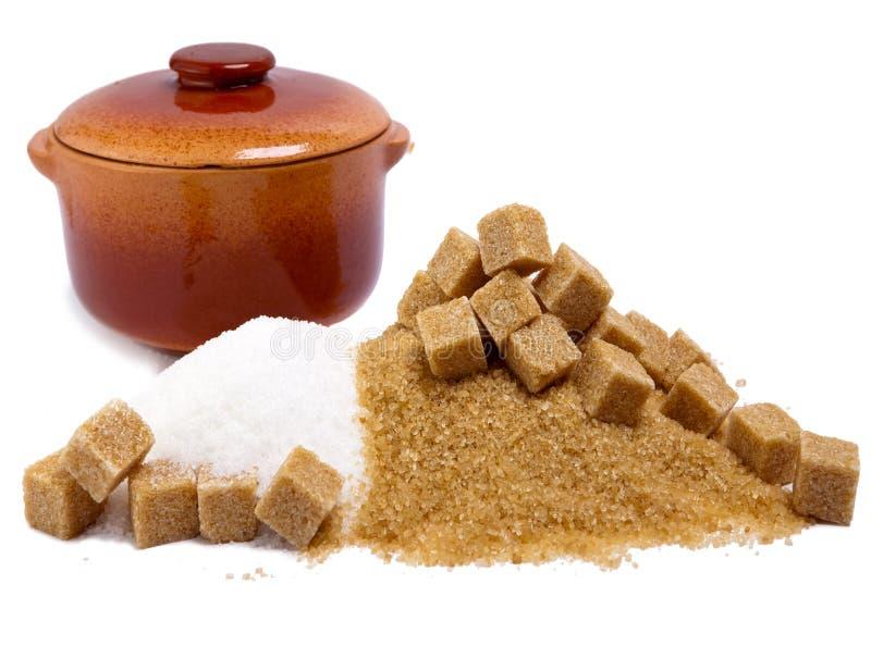 Caña refinada y marrón del azúcar granulado y cacerola de cerámica imagen de archivo libre de regalías