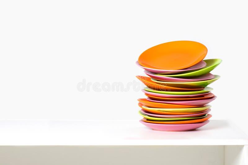 Caótico la pila de placas del color en una tabla imagenes de archivo
