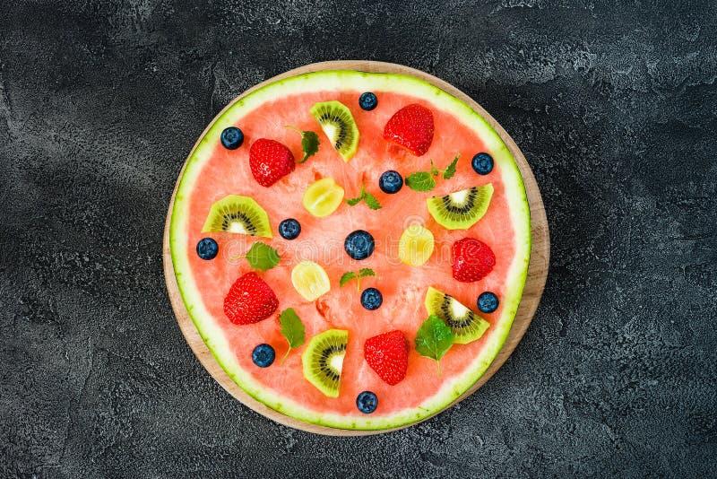 Cała arbuz pizza z owoc, ciemny tło, odgórny widok obraz stock