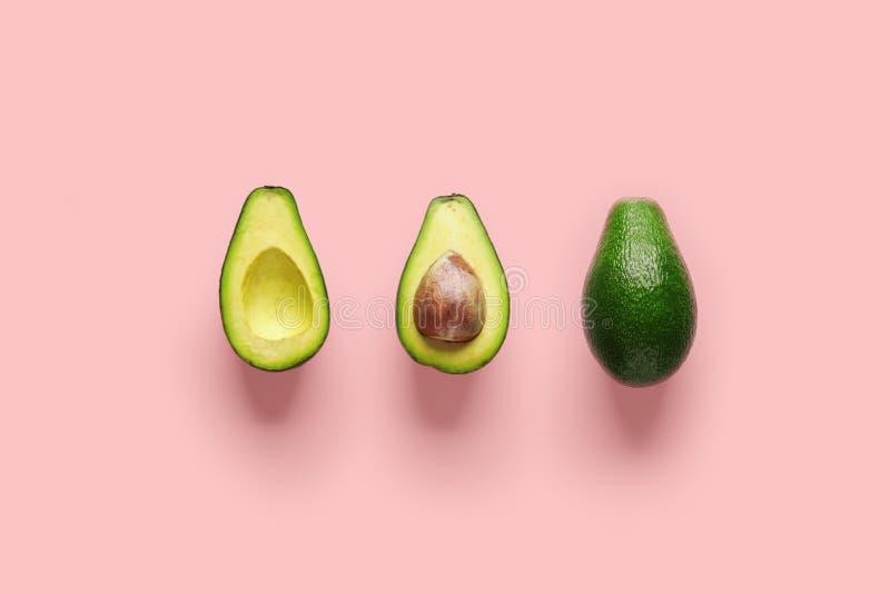 Cała avocado owoc i dwa połówki odizolowywających na różowym tle z rzędu zdjęcie royalty free