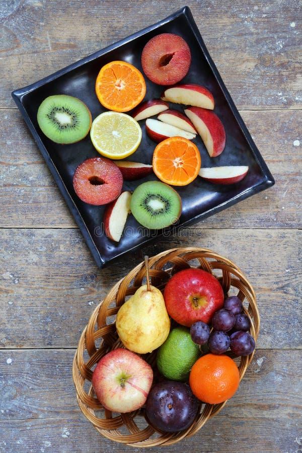 Całe i pokrojone owoc na nieociosanym drewno stole - pionowo portreta tryb obraz royalty free