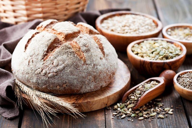 Całość zbożowego chleba z ziarnami słonecznik, bania, len i konopie, obrazy stock