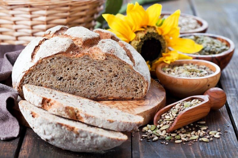 Całość zbożowego chleba z ziarnami słonecznik, bania, len i konopie, zdjęcia stock