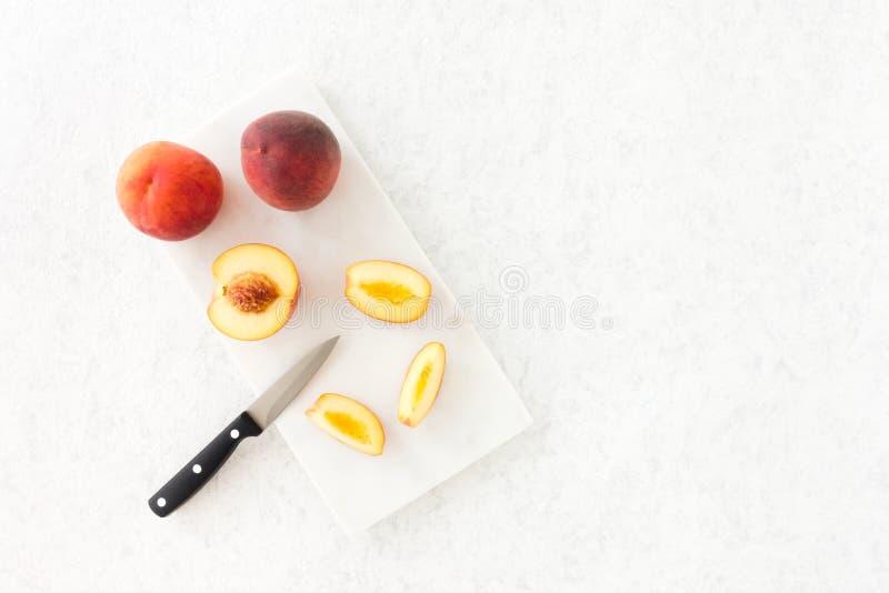 Całości i cięcia rumiena Złociste brzoskwinie na Marmurowej ciapanie desce zdjęcie stock