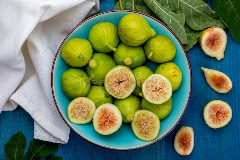 Całości i cięcia zieleni figi z figą, opuszczają zdjęcia royalty free
