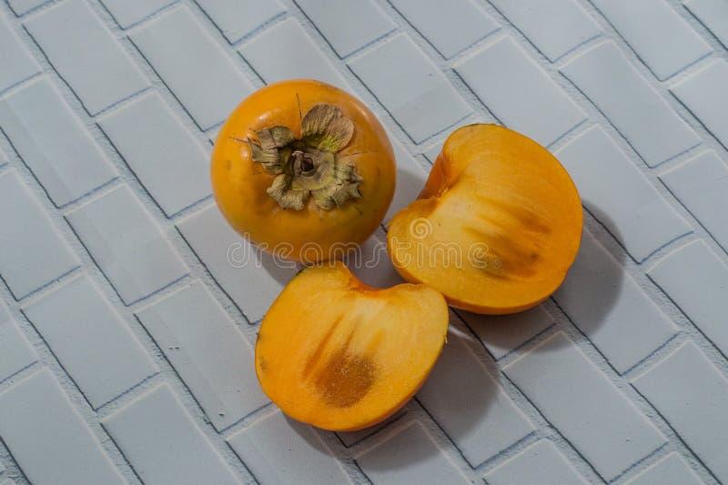 Całości lub cięcia persimmon na lekkim tle obraz royalty free