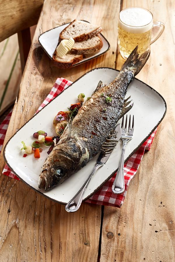 Ca?y piekarnik piec dennego basu ryba na talerzu obraz stock