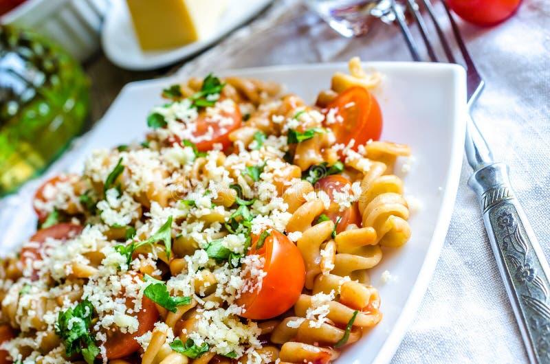 Cały pszeniczny fusilli makaron z serowymi i czereśniowymi pomidorami fotografia royalty free