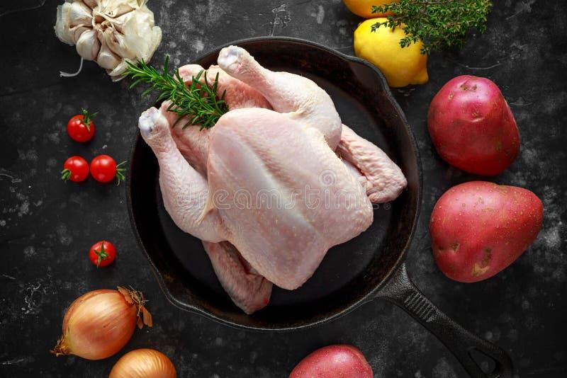 Cały surowy Bezpłatny pasmo kurczak w nieociosanej rynience z rozmarynowym liściem, macierzanką, cytryną, czerwonymi grulami i cz zdjęcie stock