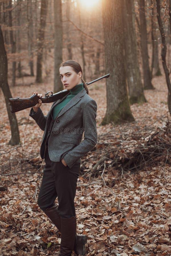 Ca?a bem sucedida Esporte da ca?a caçador da menina na menina da floresta com rifle ca?a da persegui??o Loja de arma Forma milita imagens de stock