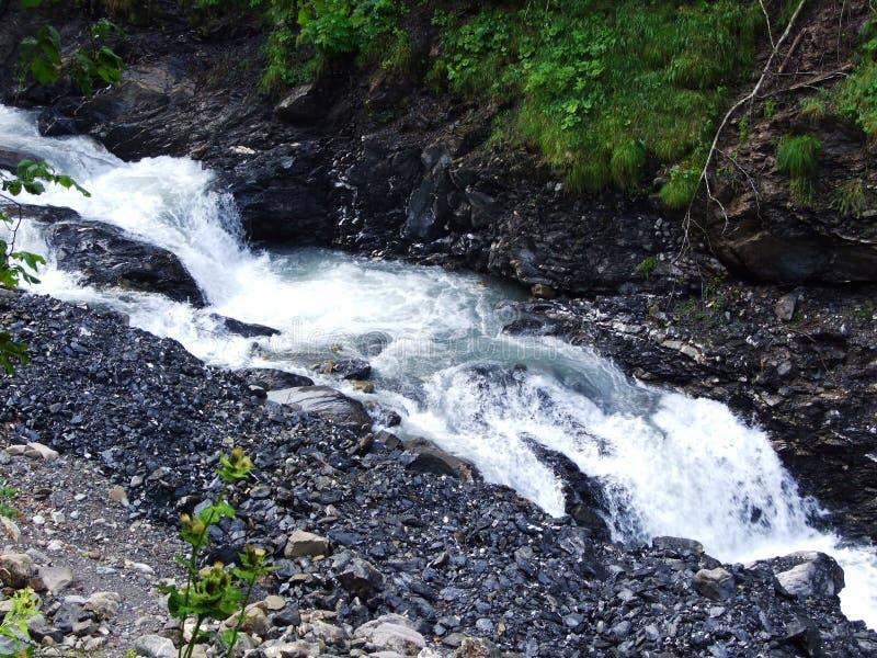 Ca?das y cascadas en la corriente de Jetzbach en el valle alpino Im del lago foto de archivo libre de regalías