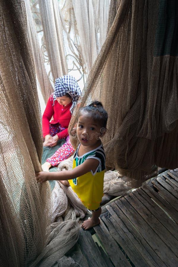 Ca Mau, Vietname - 6 de dezembro de 2016: Família de Fisher com a filha que joga perto de sua rede de carcaça da emenda da mãe em fotos de stock