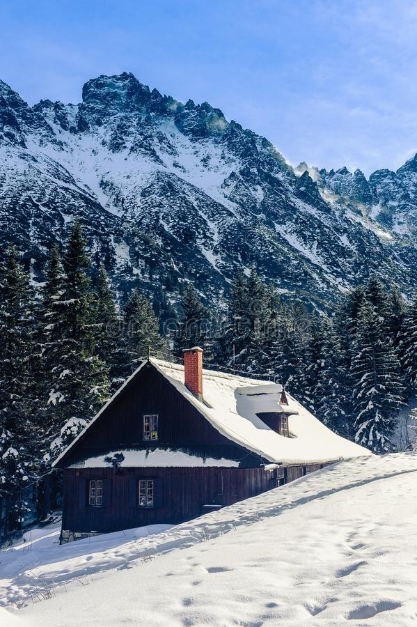 Cabaña de madera en las montañas cubiertas con nieve imagenes de archivo