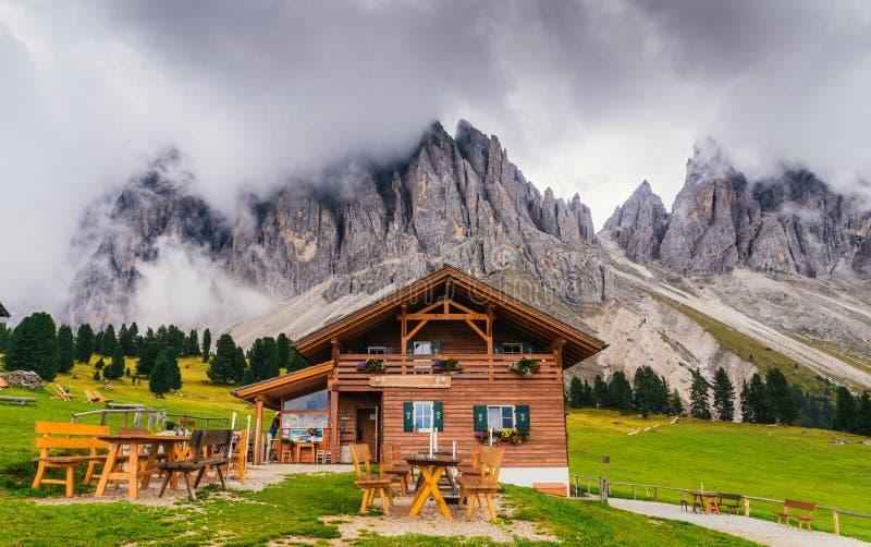 Cabaña de madera que pasa por alto la formación de roca impresionante de las dolomías en Italia septentrional fotografía de archivo