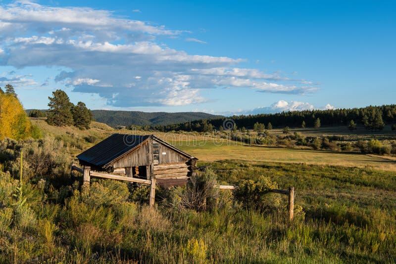 Cabaña de madera rústica vieja que pasa por alto un paisaje del ranchland, de campos, del bosque, y de colinas en el oeste americ foto de archivo
