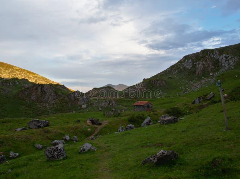 Cabaña de piedra solitaria en la cima de una montaña Al atardecer 库存照片