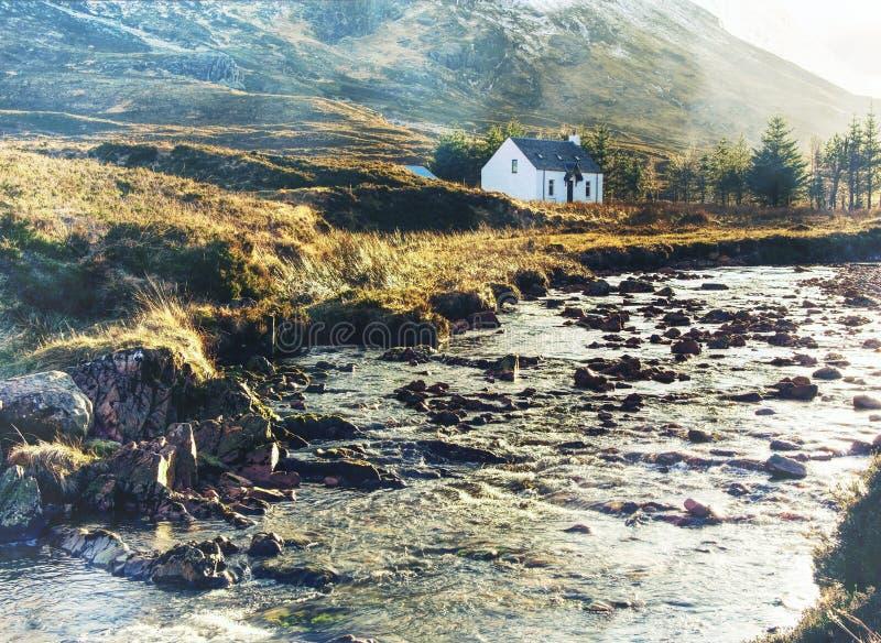 Cabaña del campo bajo en Glencoe nevoso en las montañas escocesas, fotografía de archivo libre de regalías