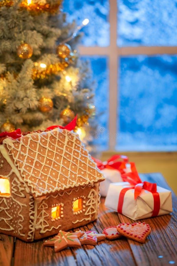 Cabaña, galletas y árbol de navidad del pan de jengibre con la ventana congelada azul fotos de archivo