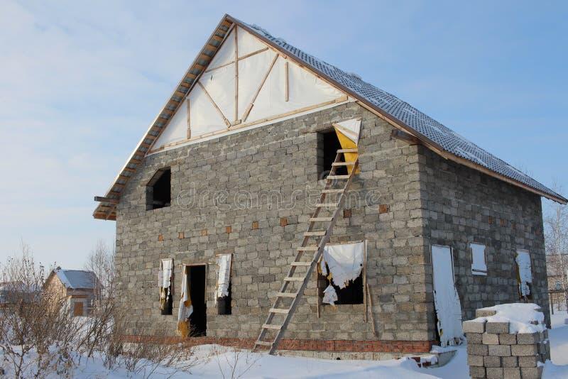 Cabaña inacabada grande de la casa de unidades de creación con Windows abierto en invierno fotografía de archivo