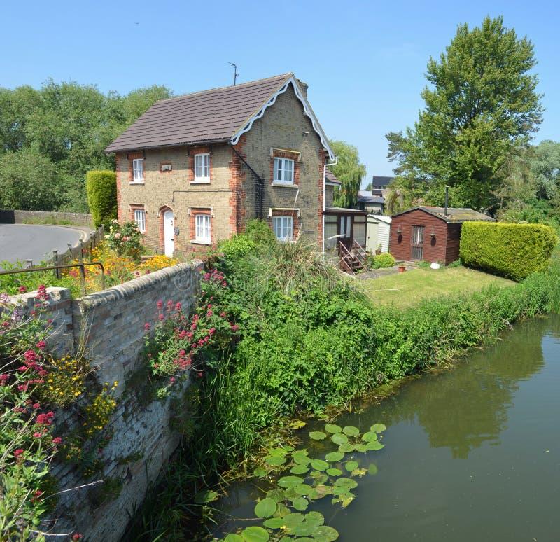 Cabaña inglesa con el jardín colorido de la cabaña y pared en los bancos del río Ouse fotos de archivo